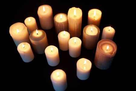 commemorate: mourning and commemoration concept - candles burning in darkness over black background