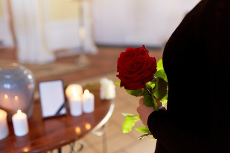 woman with roses and cremation urn at funeral