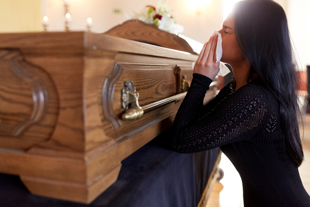 woman with coffin crying at funeral in church Stock Photo
