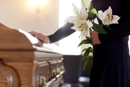 Vrouw met lelie bloemen en kist op begrafenis Stockfoto - 81277080