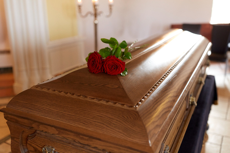 red rose flowers on wooden coffin in church Stock Photo - 81277081