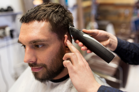 man and barber hands with trimmer cutting hair