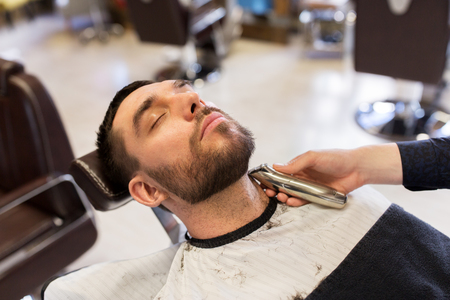 grooming: man and barber with trimmer cutting beard at salon Stock Photo