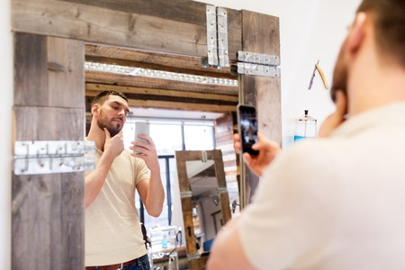 grooming: man taking selfie by smartphone at barbershop