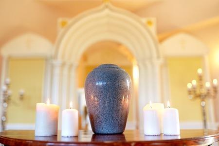 crematie urn en kaarsen branden in de kerk Stockfoto