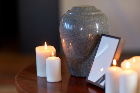 photo frame, cremation urn and candles on table