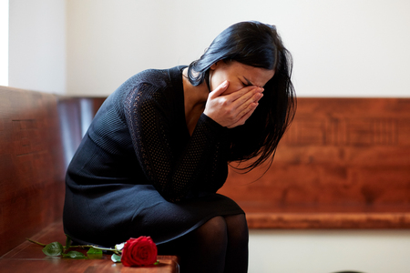 crying woman with red rose at funeral in church