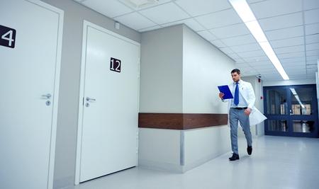 corridors: doctor with clipboard walking along hospital