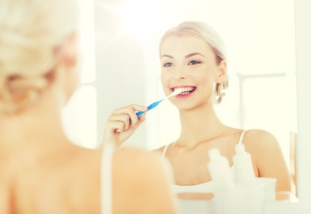 hygienic: woman with toothbrush cleaning teeth at bathroom
