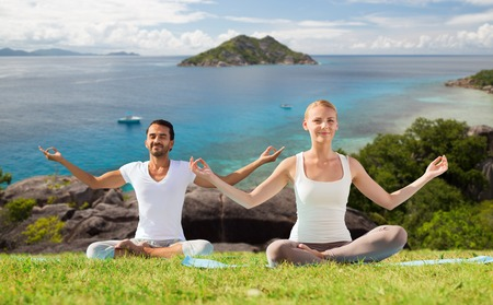 happy couple doing yoga and meditating outdoors Imagens
