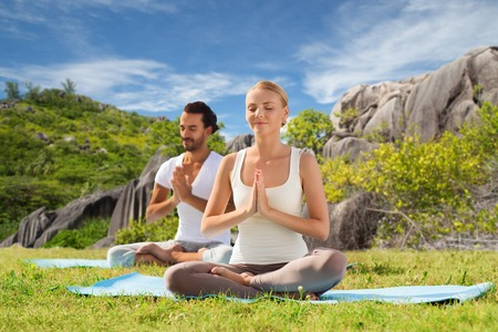 happy couple doing yoga and meditating outdoors Stock Photo