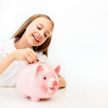 thrifty: happy smiling girl putting coin into piggy bank Stock Photo