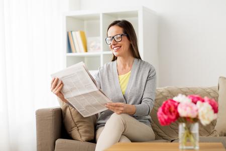 massamedia en mensenconcept - de gelukkige krant van de vrouwenlezing thuis Stockfoto
