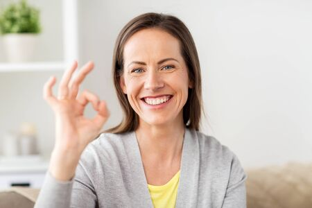 people and gesture concept - happy smiling middle aged woman showing ok hand sign at home Stock Photo