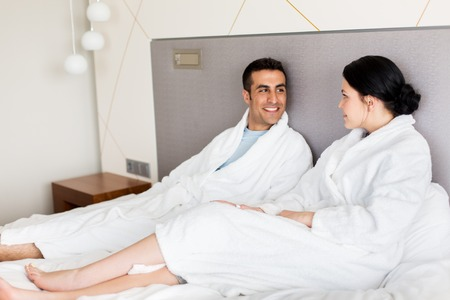 people, leisure and vacation concept - happy couple in bed at home or hotel room