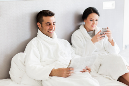 people, leisure and vacation concept - happy couple with newspaper and smartphone in bed at home or hotel room
