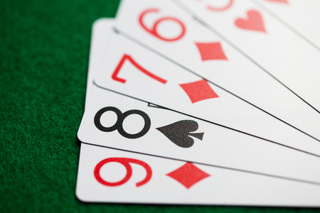 casino, gambling, games of chance, hazard and entertainment concept - straight poker hand of playing cards on green cloth Stock Photo