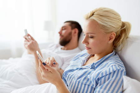 people, technology and communication concept - couple with smartphones in bed at home