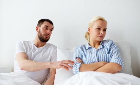 사람, 관계 어려움 및 가족 개념 - 집에서 침대에서 충돌하는 불행 한 부부