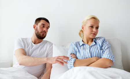 lovers quarrel: people, relationship difficulties and family concept - unhappy couple having conflict in bed at home Stock Photo
