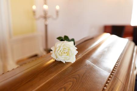 begrafenis en rouwconcept - witte roos bloem op houten kist in de kerk Stockfoto