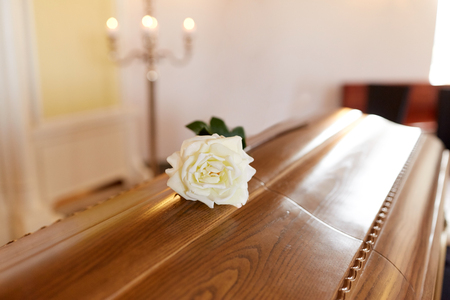 funeral and mourning concept - white rose flower on wooden coffin in church
