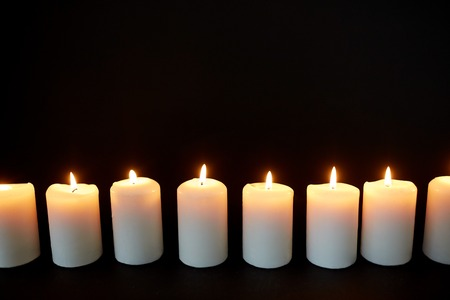candles burning in darkness over black background Imagens