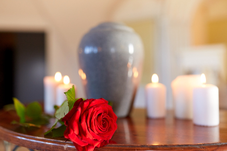 red rose and cremation urn with burning candles