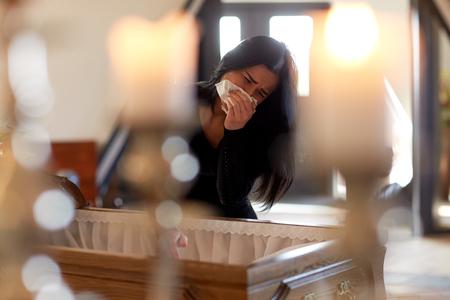 Vrouw met een kist die bij de begrafenis in de kerk huilt Stockfoto