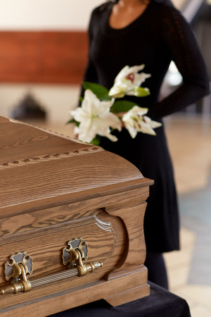 woman with flowers and coffin at funeral Stock Photo
