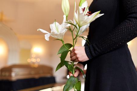 Mensen en rouwconcept - close-up van vrouw met witte lelie bloemen en doodskist bij begrafenis in de kerk Stockfoto