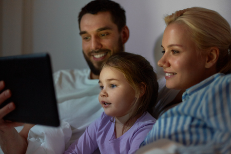 people, family and technology concept - happy mother, father and little girl with tablet pc computer in bed at night home photo