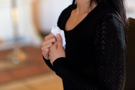 Mensen, verdriet en rouwconcept - close-up van vrouw met afveeg bij begrafenis in de kerk Stockfoto