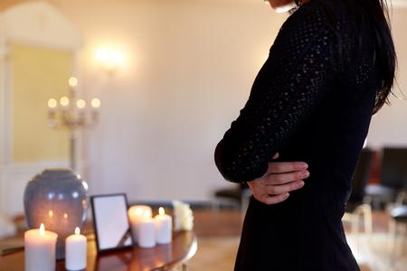 Crematie, mensen en rouwconcept - close-up van vrouw met cinerary urn en fotolijst bij begrafenis in de kerk