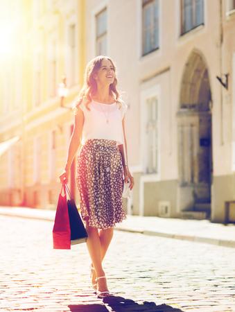 販売、消費者と人々 のコンセプト - 街の通りに沿って歩いて買い物袋を持つ幸せな若い女性