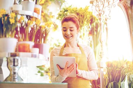 las personas, los negocios, la tecnología, la venta y la floristería y el concepto - mujer feliz floristería sonriendo con ordenador Tablet PC en la tienda de flores