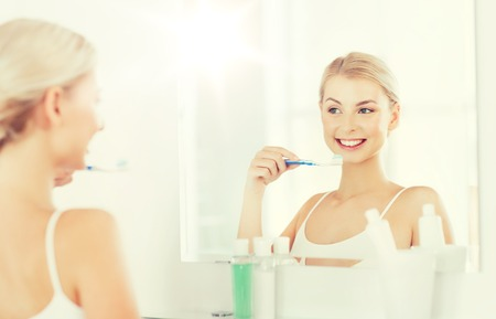 whiten: health care, dental hygiene, people and beauty concept - smiling young woman with toothbrush cleaning teeth and looking to mirror at home bathroom