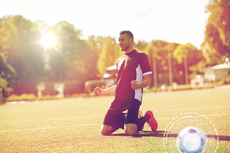 sport, success and people - happy soccer player with on football field