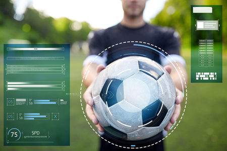 sport, football training and technology - soccer player hands holding ball on field