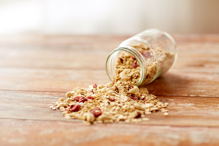 food, healthy eating and diet concept - jar with granola or muesli poured on wooden table Zdjęcie Seryjne