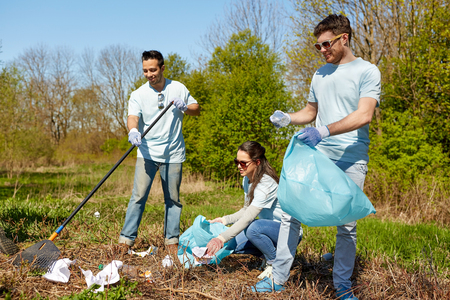 volunteering, charity, people and ecology concept - group of happy volunteers with garbage bags and rake cleaning area in park Imagens - 81080299