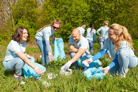 participate: volunteering, charity, people and ecology concept - group of happy volunteers with garbage bags cleaning area in park Stock Photo