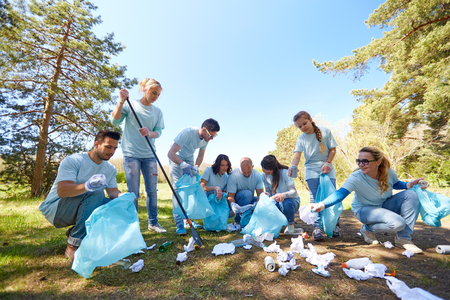 participate: volunteering, charity, people and ecology concept - group of happy volunteers with garbage bags and rake cleaning area in park