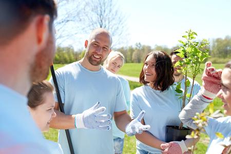 selfless: volunteering, charity, people and ecology concept - group of happy volunteers with tree seedlings talking in park