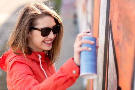people, street art and creativity concept - happy smiling young woman or teenage girl drawing graffiti with spray paint on wall Stock Photo