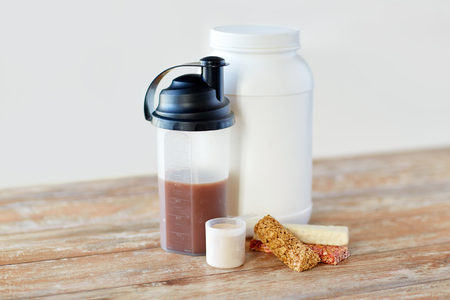 sports nutrition, fitness diet and food concept - jar, protein shake bottle and muesli bars on wooden table