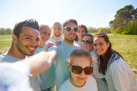 volunteering, charity and people concept - group of happy volunteers taking selfie by smartphone in park