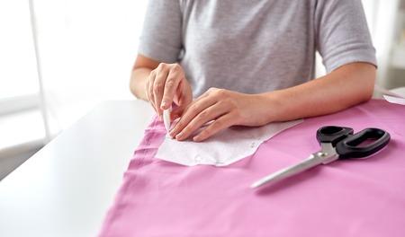 人々、ステッチ、縫製、仕立てのコンセプト - 型紙と縫製工房ファブリック上の描画チョーク調整女性