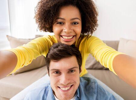 happy multiethnic couple taking selfie at home
