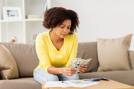african woman with papers and calculator at home